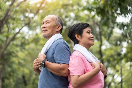 Ritratto di coppia senior asiatica in piedi su sfondo verde della natura. Uomo anziano e donna che si esercitano insieme al parco all'aperto.