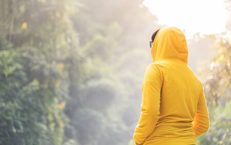 Happy woman traveler in yellow sweater with hood is standing and looking to nature on vacation concept. Rear view.
