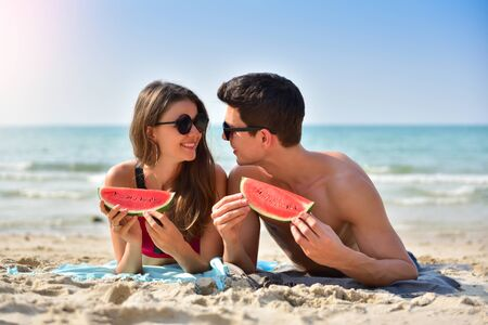 Relaxing young Couple wear sunglasses holding slice of watermelon while lying on the beach. Stock Photo