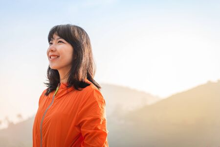 Portrait Asian woman in orange jacket is smiling and standing over mountain background. Vision, Successful, Positive emotion.