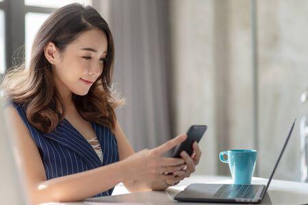 Sonriente empresaria asiática con smartphone. Foto de archivo