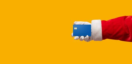 Santa Claus hand holding blue credit card on yellow or orange isolated background. Shopping, Sales, Giving Gift for Black Friday, Christmas and New Year 2019 concepts.