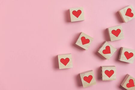 Heart in Wooden cubes on pink background with copy space. Standing out, Contrast, Difference, Valentine's day concepts.