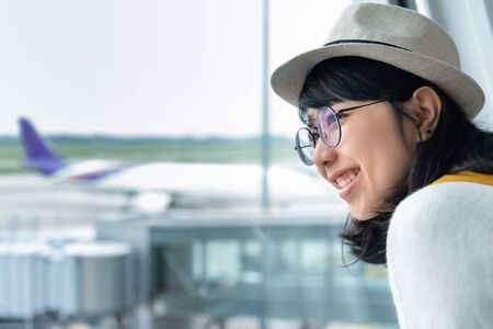 Happy Young Asian woman wear eyeglasses and hat with a beautiful smile is enjoying in her trip at the airport. Looking away. Positive emotion. Zdjęcie Seryjne