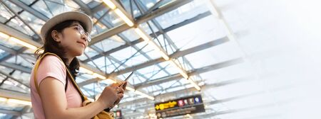 Portrait of young woman traveler wear glasses and hat with backpack traveling on weekends. Confident Asian girl passenger holding smartphone while looking away in the airport. Happy smiling Female passenger in pink casual cloth waiting for the flight. Journey, Holiday maker. Imagens