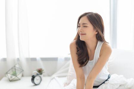 目を閉じた美しいアジアの笑顔の女性は自宅でベッドでリラックス。長い髪の白いパジャマを着たハッピーチャーミングシャイガールの肖像画が目を覚まし、朝に空気を吸います。気楽な、ポジティブな感情、表情の顔。