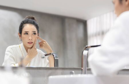 Stressed Asian woman in white Bathrobe looking at pimple on face into the mirror and try to squeeze it. Worried Young Beautiful girl try to remove her acne in bathroom. Skin care concept.