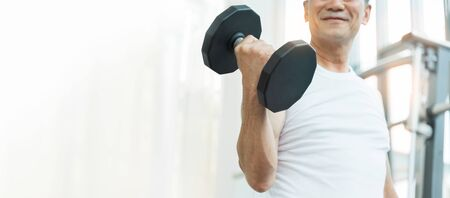 Happy Asian Senior Fitness man lifting dumbbell while exercise at the gym. Strong Sporty Elderly male in white sportswear smiling while workout. Lifestyle, Healthy. Banner, Web.