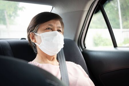 Asian Senior woman Passenger wear protective or surgical mask for prevent coronavirus or Covid-19 while sitting in car. Protection for Germs and virus pandemic in Public transportation. Sanitation, Healthy and Health care concept.