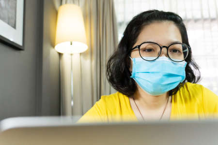 Happy Asian female wear eyeglasses using laptop computer during quarantine, isolated. Young Woman in yellow shirt wear blue surgical mask working from home during pandemic virus. Covid-19, Coronavirus, Healthy, Prevention, Protection. Reklamní fotografie
