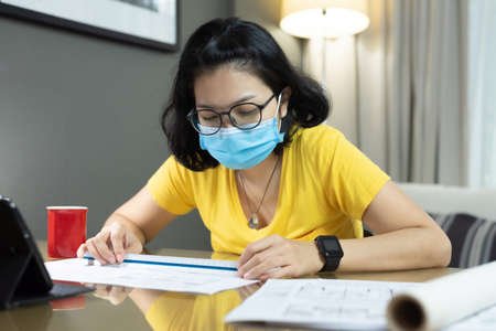 Asian female Architect wear eyeglasses using scale ruler for measurement on her blueprints during quarantine in pandemic Coronavirus. Young Woman interior designer in yellow shirt, blue surgical mask working from home during Covid 19. Reklamní fotografie