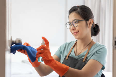 Attractive Asian Woman in orange rubber gloves wipe on door, doorknob with alcohol cleaning spray at the house. Beautiful smiling Housewife with housework. Coronavirus, COVID-19 Stok Fotoğraf