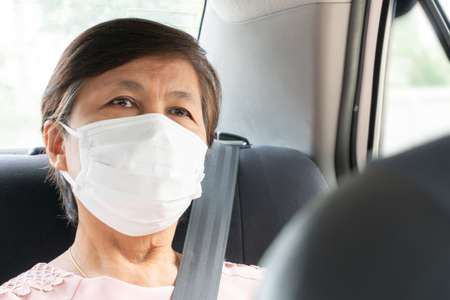 Asian elderly woman Passenger wear surgical mask for prevent coronavirus or Covid-19 while sitting in car. pandemic virus in Public transportation. Life, Health care concept.