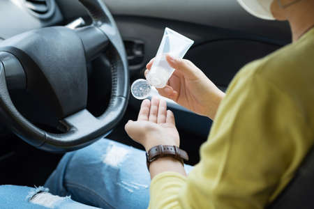 Asian woman in green shirt using hand sanitizer alcohol gel washing and cleaning her hands for prevent Covid-19 or Coronavirus before driving a car. Antiseptic, Hygiene, Health care