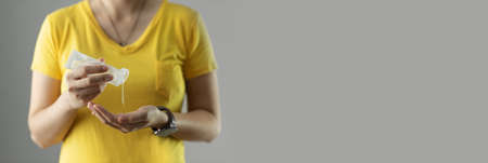 Asian Woman in yellow shirt standing over grey background is pouring portable hand sanitizer gel on her palms for prevent coronavirus or Covid-19. Pandemic, Antiseptic, Hygiene, Health care. Banner, Panoramic Imagens