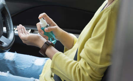 Asian woman in green shirt using alcohol spray washing and cleaning her hands for prevent Covid-19 or Coronavirus before driving a car. Hand sanitizer, Antiseptic, Hygiene, Health care