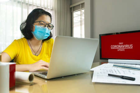 Asian female Creative wear eyeglasses making online video meeting with laptop computer during quarantine. Young Architect designer Woman in yellow shirt wear blue surgical mask working from home during pandemic virus. Covid 19, Coronavirus, Health care