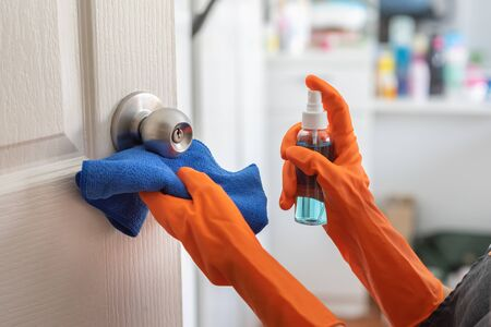 Woman wear orange rubber gloves cleaning door, doorknob with alcohol spray at the house. Disinfection for hygiene. Coronavirus, COVID-19
