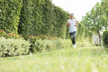 Happy Healthy Asian Senior man enjoying workout at outdoor with copy space. Portrait of Smiling Elderly male jogging exercise at the park. Health, Lifestyle, Wellness.   Фото со стока