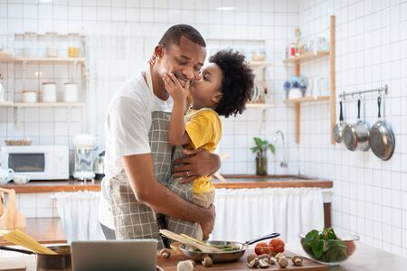 African Cute little boy in yellow casual kissing Dad while cooking at home together. Happy smiling African-American Father while hug and carry his son in kitchen. Joyful Black family, Love emotion. Reklamní fotografie