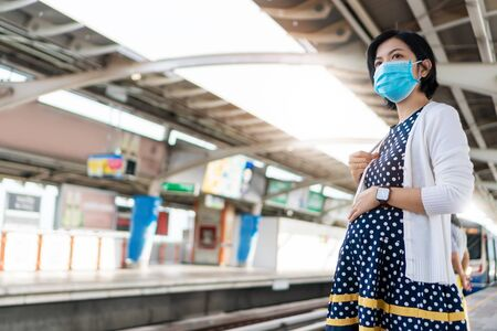 Asian Pregnancy Woman wearing face mask waiting sky train while going to office. Young mother in public transportation during pandemic virus. Health care in New normal and social distancing.