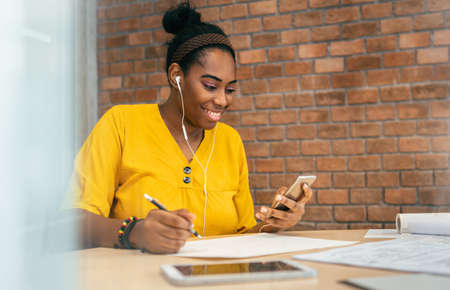 African woman designer using smartphone and earphones for listening to music while working at workplace. African-American Creative Female in Yellow shirt enjoying online video chat with mobile phone Imagens