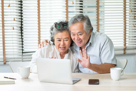 Happy Asian Senior Couple making video chat and waving hands to their family on laptop at home. Smiling Elderly man and woman enjoy with internet technology on notebook together, Mature lifestyle