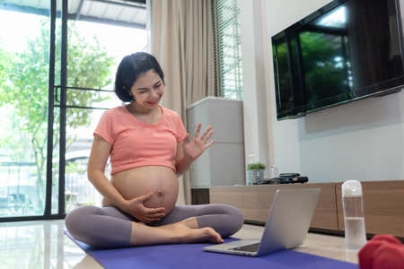 Beautiful Asian Pregnant woman making video call online on laptop while her pregnancy at home. Happy smiling Young Mother enjoying talking and waving hand to family while doing yoga exercise