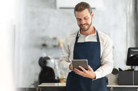 Portrait of a Hipster barista in blue apron using digital tablet standing at the bar of the modern cafes. Smiling attractive Bearded man receiving hot drink online orders with service mind