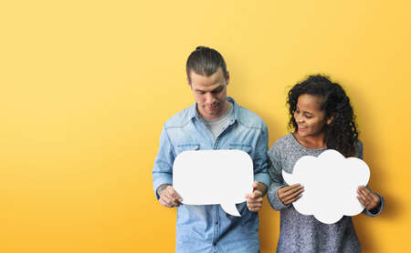 Portrait Hipster African American male and female in casual standing holding and looking at white blank speech bubble over isolated yellow background. Happy Diversity couple holding with smiling face Stock Photo