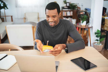 Black African American male using laptop celebrating birthday online by video chat with birthday cake at home.