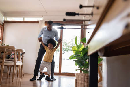 Happy Smiling African Dad holding hands and helping little Adorable child stepping with his shoe at home. Cheerful Black Father and Son playing together.