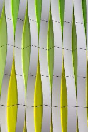 Detail of a modern facade with curved elements in silver color, green and yellow photo