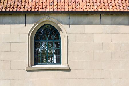 dwelling mound: Church wall with a pointed arch window Stock Photo