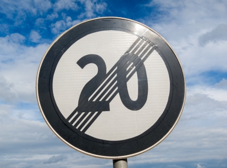 End of speed limit 20 against cloudy sky photo