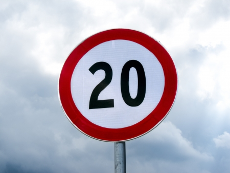 miles: Speed limit sign 20 on a pole against cloudy sky