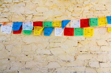 Buddhist tibetan prayer flags against stone wall