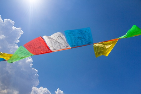 Few buddhist tibetan prayer flags against blue sky with a cloud