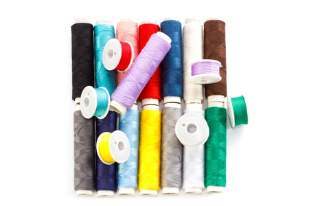 abreast: Several multicolored bobbins and coils with sewing thread isolated on white background