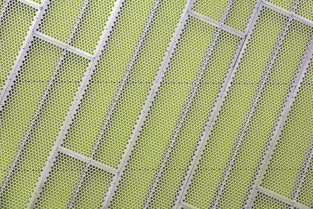 Steel facade cladding with a mesh of holes on a green wall Stock Photo - 16127067