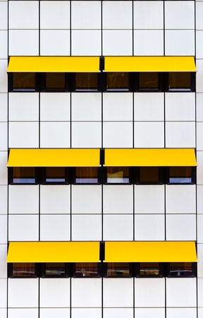 awnings: Crop of modern facade with white tiles and yellow awnings