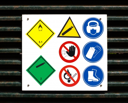 Danger and safety symbols on rusty door to gas storage. Stock Photo - 16127047
