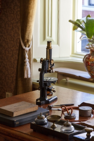 old times: Old microscope on the desk of the doctor in ancient times