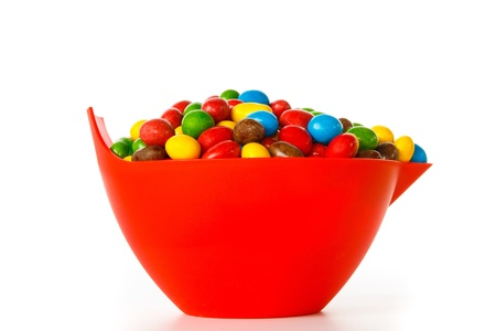 Bowl with colorful chocolate sweets against white background photo