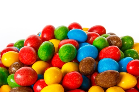 Closeup of a pile of colored chocolate sweets against white background photo
