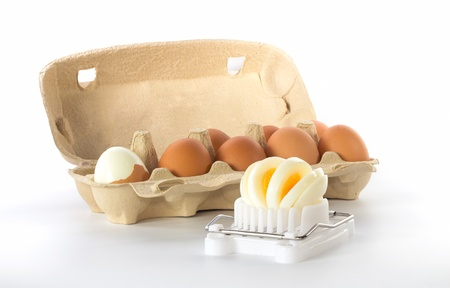 Egg slicer with a box of eggs with one half peeled egg photo
