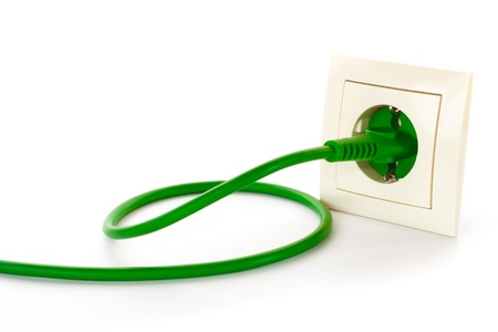 Green power plug into power outlet against a white background photo
