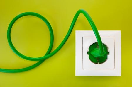 electricidad: Enchufe verde en la toma del poder blanco sobre un fondo verde oliva