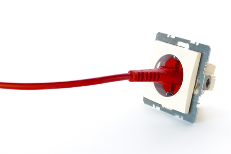 Red power cable plugged into wall outlet against white background