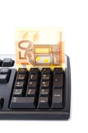 teclado numerico: Billetes se inserta en el teclado de ordenador para el pago en línea, aislado en blanco Foto de archivo